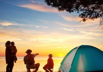 Family camping in tent with sunset in the background
