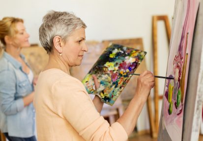 senior woman painting at art school studio