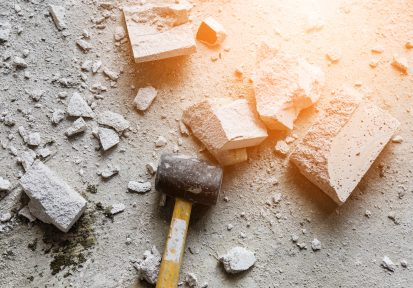 Business trouble and fear overcome concept. hammer smash with light brick mass break apart construction.