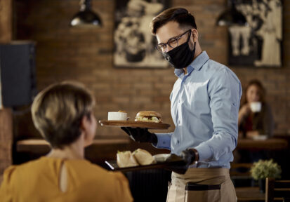 Happy waiter serving food to a guest while wearing protective face mask and gloves in a pub.