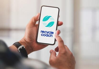 Close up view of a man using the recycle coach app on his cell phone