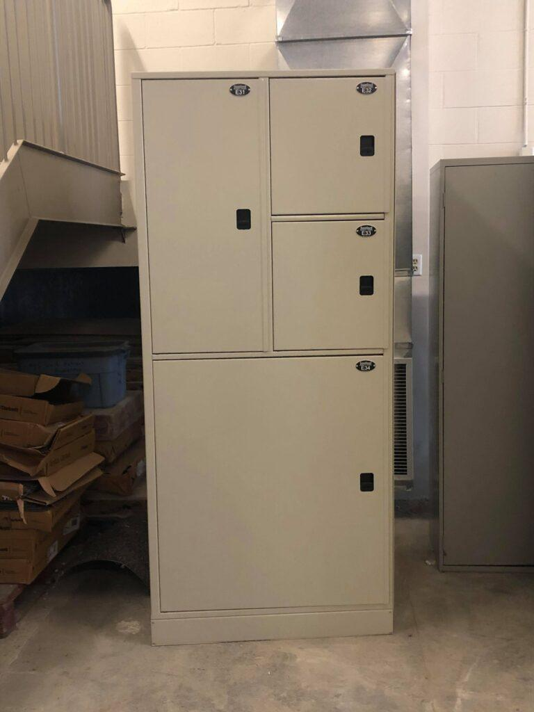 Photo of a light grey large steel locker with 4 compartments. This image is being presented to advertise the sale of this item as a municipal surplus equipment.