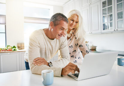 Couple looking at computer in their kitchen